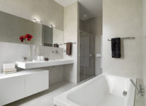 32686598 - panoramic view of a modern bathroom with washbasin and bathtub